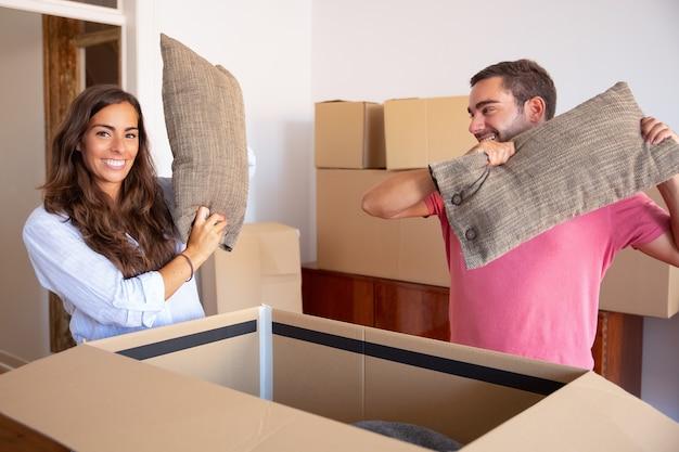 Positieve opgewonden jonge man en vrouw die kussens van open kartonnen doos uitstappen, genieten van het verplaatsen en uitpakken van dingen Gratis Foto
