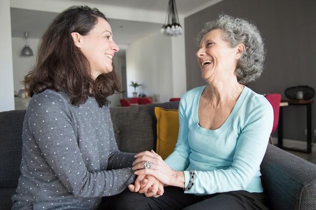 Positieve oudere vrouw en haar dochter chatten, lachen Gratis Foto