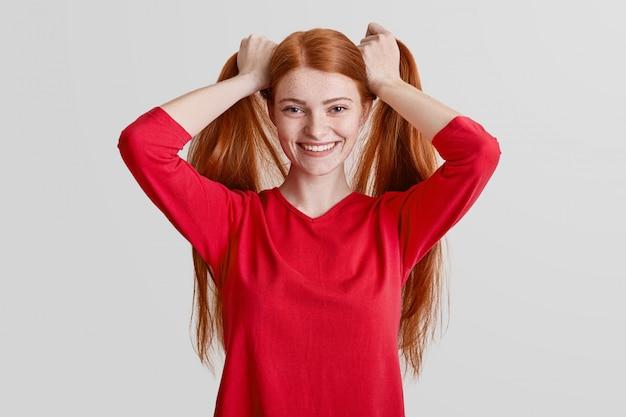 Positieve roodharige vrouw met sproeten heeft lang haar, maakt paardenstaarten, poseert graag voor de camera en draagt een rode casual trui Gratis Foto
