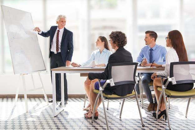 Positieve senior leader tekening grafiek op vergadering Gratis Foto