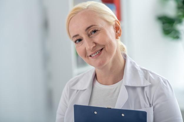 Positieve stemming. blonde en arts die op middelbare leeftijd positief glimlacht kijkt Premium Foto