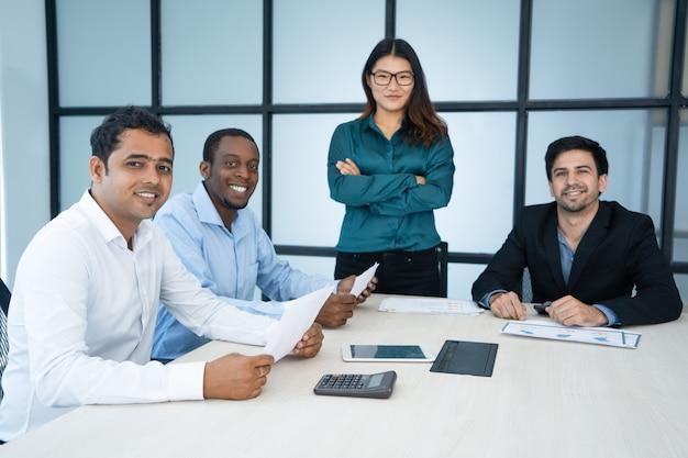 Positieve succesvolle internationale team bedrijfseconomische analyse op vergadering. Gratis Foto