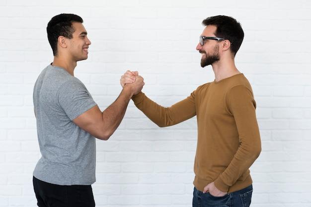 Positieve volwassen mannen die handen houden Gratis Foto
