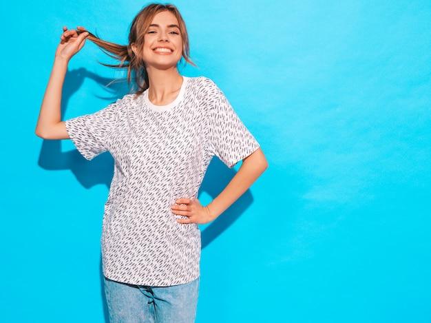 Positieve vrouw die lacht. het grappige model stellen dichtbij blauwe muur in studio. zij raakt haar haar Gratis Foto
