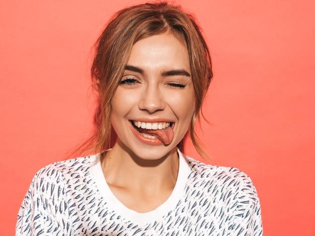 Positieve vrouw die lacht. het grappige model stellen dichtbij roze muur in studio. toont tong en knipoogt Gratis Foto