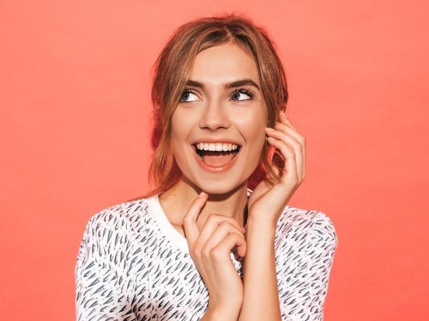 Positieve vrouw die lacht. het grappige model stellen dichtbij roze muur in studio Gratis Foto