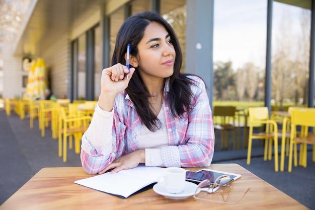 Positieve vrouw die nota's in openluchtkoffie maakt Gratis Foto