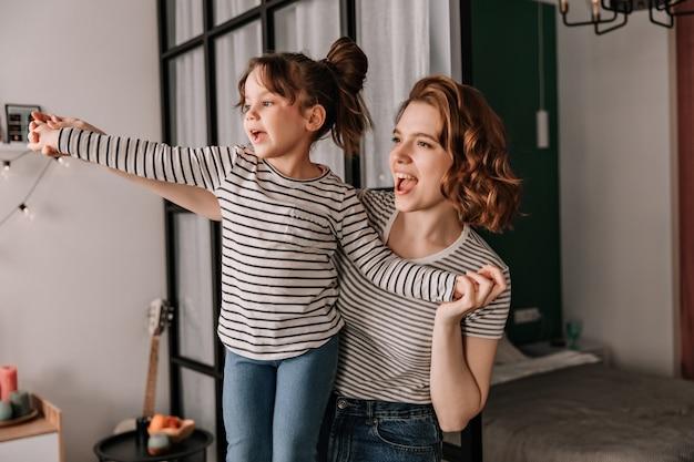 Positieve vrouw en haar dochter in gestreepte t-shirts lachen en dansen in appartement. Gratis Foto