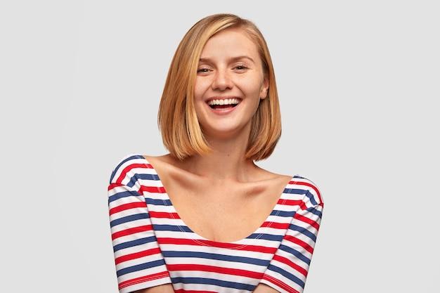 Positieve vrouw met brede glimlach, toont witte tanden, lacht om een goede grap, houdt van grappig verhaal van gesprekspartner, heeft een slank lichaam, gekleed in een gestreepte jas Gratis Foto