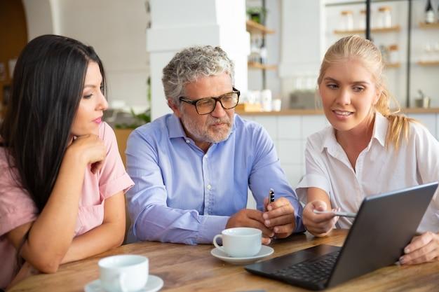Positieve vrouwelijke agent projectpresentatie op laptop tonen aan jonge vrouw en volwassen man, wijzende pen op display, details uit te leggen Gratis Foto