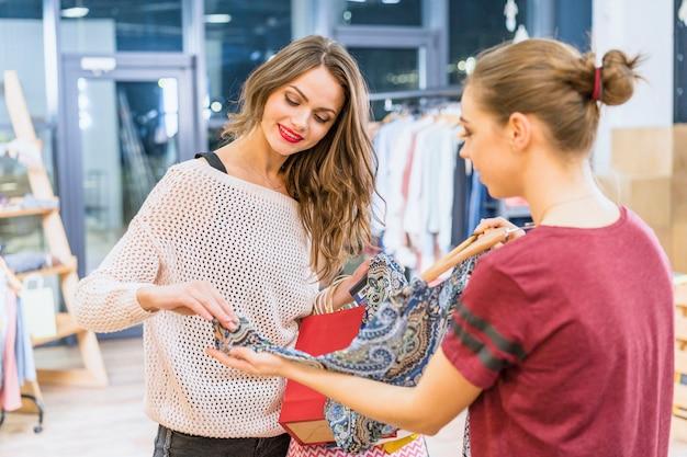 Positieve vrouwelijke assistent die jonge klant in kledingsboutique dient Gratis Foto