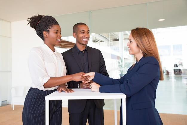 Positieve vrouwelijke partners die handen schudden Gratis Foto