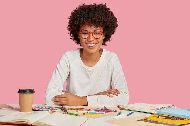 Positieve vrouwelijke vermenigvuldiger met afro-kapsel, aangename glimlach op het gezicht, geniet van haar werk, heeft echt talent voor het maken van illustraties, geniet van warme dranken, geïsoleerd over roze muur. creativiteit concept Gratis Foto