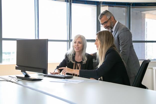Positieve zakencollega's kijken naar presentatie op pc-monitor, project bespreken, zitten op de werkplek en wijzen op display. zakelijke communicatie concept Gratis Foto