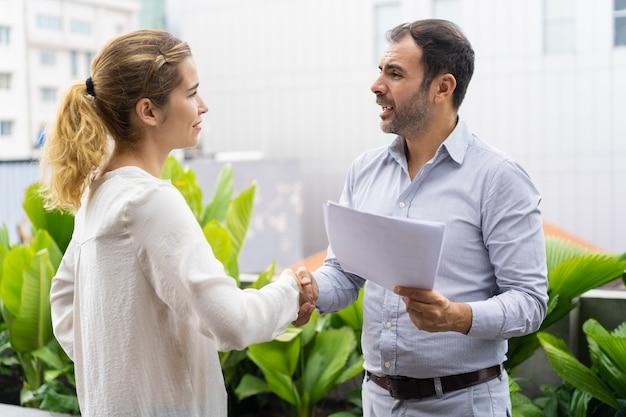 Positieve zakenpartners die vergadering met handdruk beëindigen Gratis Foto