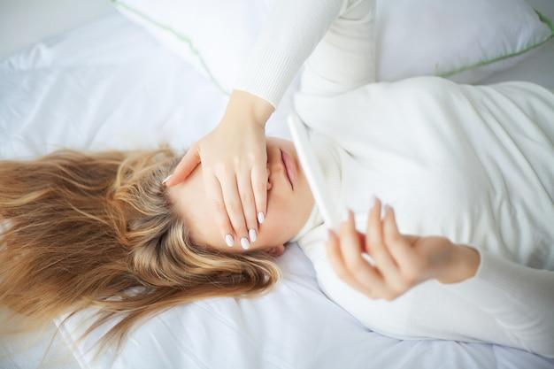 Positieve zwangerschapstest. jonge vrouw die depressief en droevig voelen na thuis het bekijken het resultaat van de zwangerschapstest Premium Foto