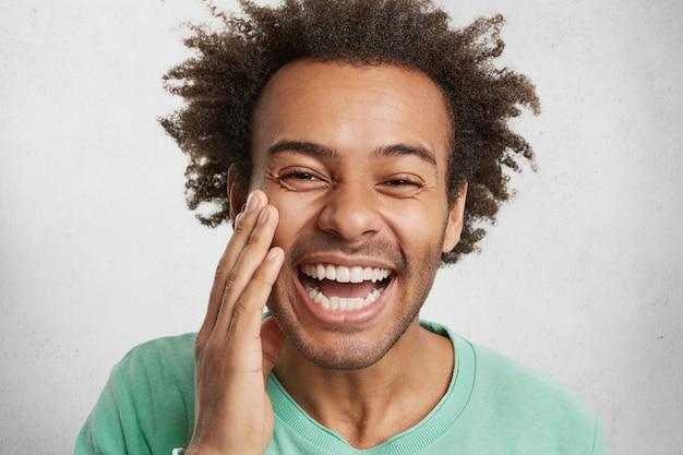 Positiviteit en prettige emoties concept. blij man met een donkere, gezonde huid grijnst Gratis Foto