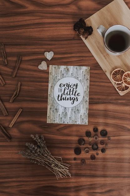 Poster naast een kopje koffie, een kleine poster, droog gras en kleine accessoires Gratis Foto