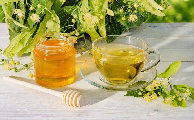 Pot lindehoning, dop van linde thee en tak met linde bloemen op een zonnige dag Premium Foto
