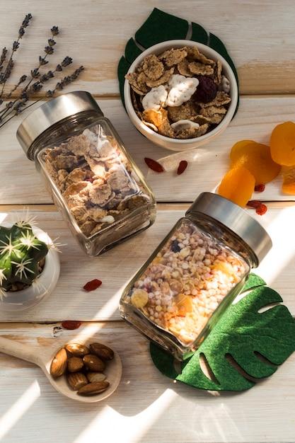 Pot met muesli; cornflakes; droge vruchten; kunstblad en vetplant op houten oppervlak Gratis Foto