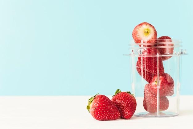 Pot met verse rode aardbeien op tafelblad Gratis Foto