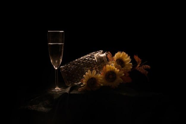 Pot met zonnebloemen en een glas champagne op tafel geïsoleerd op een zwarte achtergrond Gratis Foto
