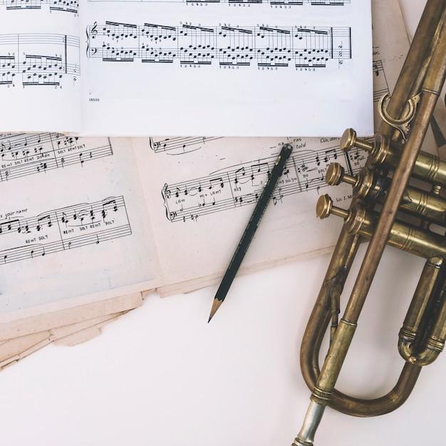 Potlood en trompet dichtbij bladmuziek Gratis Foto