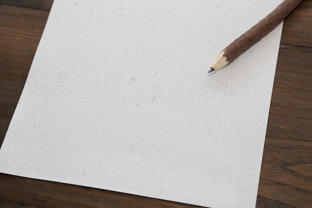 Potlood met blanco papier op oude houten tafel foto premium