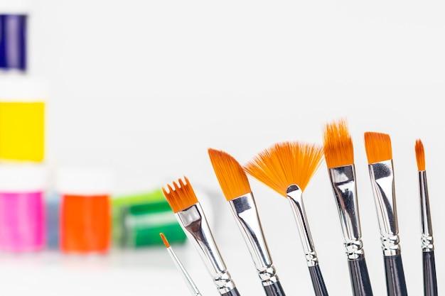 Potten met kleurrijke verf met verschillende penselen om te schilderen Premium Foto