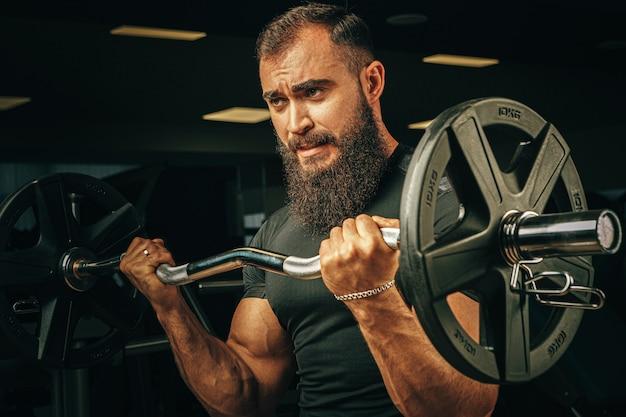Powerlifter met sterke armen tillen halter in een sportschool Premium Foto