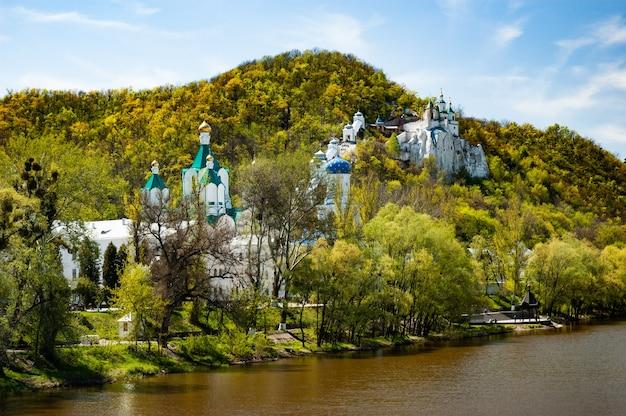 Prachtig betoverend uitzicht op de orthodoxe kerk en het klooster gelegen aan de oevers van de rivier op de heuvels bedekt met groen struikgewas op een zonnige warme herfstdag. concept van geestelijk leven Premium Foto