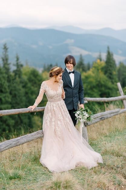 Prachtig bruidspaar zoenen en omhelzen in de buurt van de oever van een bergrivier met stenen Premium Foto