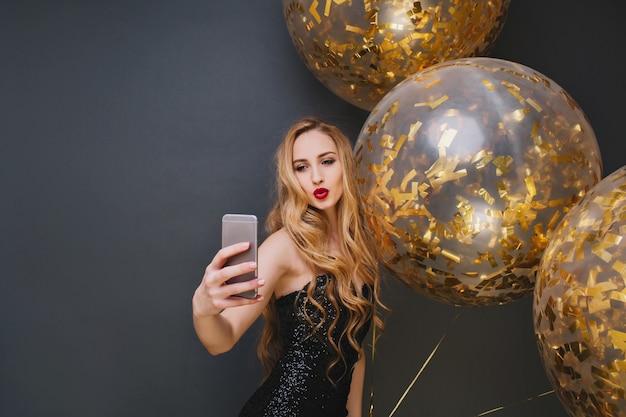 Prachtig europees meisje selfie maken met kussende gezichtsuitdrukking. prachtige jonge vrouw met lang haar verjaardagsfeestje met grote ballonnen genieten. Gratis Foto