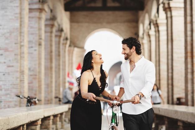 Prachtig geklede man en vrouw lopen in de oude stad met een fiets Premium Foto