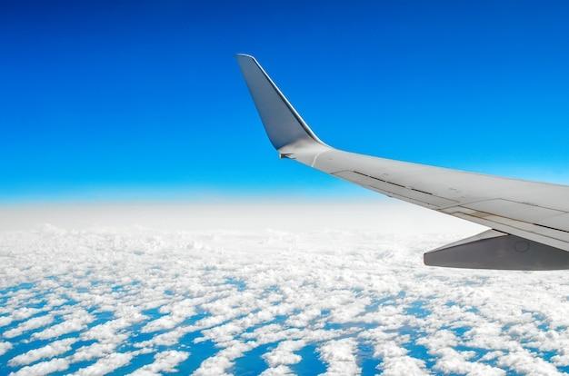Prachtig klassiek uitzicht op de patrijspoort tijdens een vlucht per vliegtuig, wolken van blauwe lucht en aarde. Premium Foto