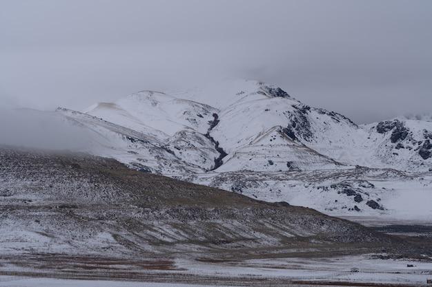 Prachtig landschap van besneeuwde bergen op een donkere sombere dag Gratis Foto