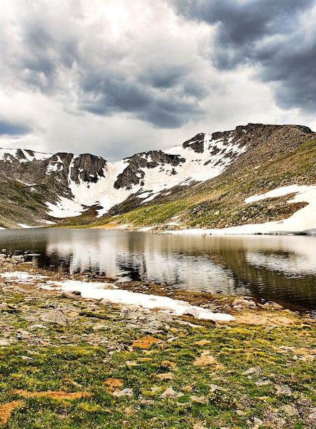 Prachtig landschap van een meer omgeven door hoge rotsachtige besneeuwde bergen onder een bewolkte hemel Gratis Foto