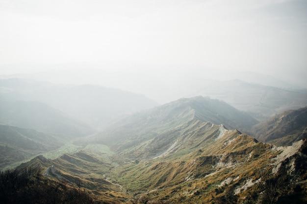 Prachtig landschap van een reeks groene bergen gehuld in mist Gratis Foto