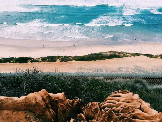 Prachtig landschap van het strand met weinig mensen geschoten vanaf een hoger terrein Gratis Foto