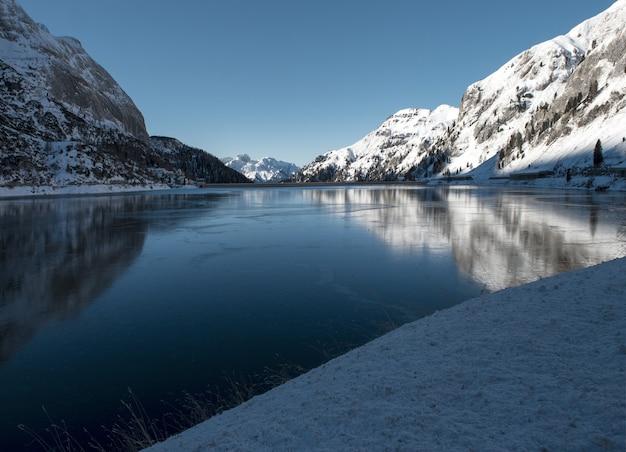Prachtig landschap van hoge met sneeuw bedekte bergen die reflecteren op het meer in de dolomieten Gratis Foto