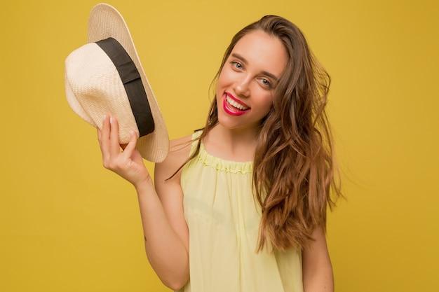 Prachtig langharig vrouwelijk model poseren op gele muur, hoed en glimlach te houden Gratis Foto