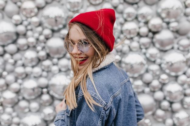 Prachtig meisje lachen in spijkerjasje geluk uitdrukken. foto van schattige dame in glazen poseren naast sparkle discoballen en kijken over de schouder. Gratis Foto