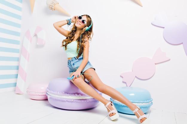 Prachtig meisje met lichtbruin glanzend haar dat van muziek geniet tijdens rust op koekjesstoel. portret van prachtige jonge vrouw trendy accessoire dragen en favoriete liedje luisteren in grote koptelefoon. Gratis Foto