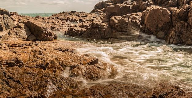 Prachtig panoramisch shot van kliffen en rotsen met een zee Gratis Foto
