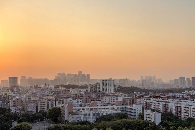 Prachtig panoramisch van stadsgebouwen onder een oranje hemel bij zonsondergang Gratis Foto