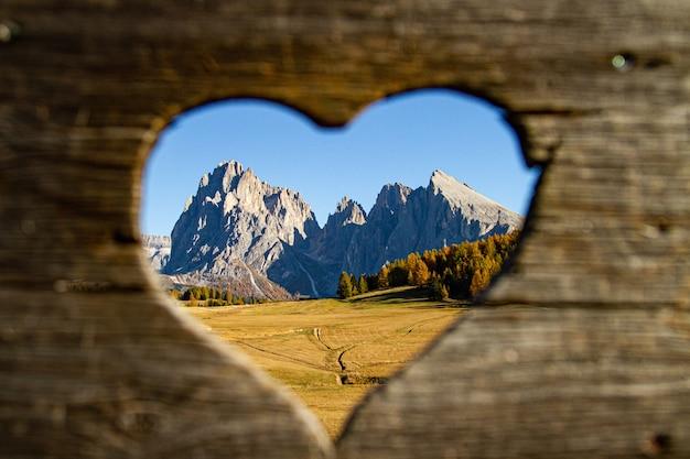 Prachtig schot van hartvormig geheel van bergen en groene bomen in de verte in dolomiet italië Gratis Foto