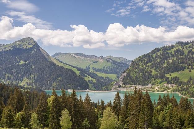 Prachtig schot van lac de l'hongrin dam met bergen onder een heldere hemel Gratis Foto
