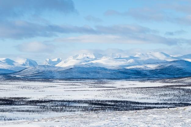 Prachtig shot van besneeuwde velden en bergen in de verte in het noorden van zweden Gratis Foto