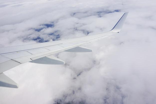 Prachtig shot van de lucht vol wolken en een vliegtuigvleugel vanuit het vliegtuigraam Gratis Foto