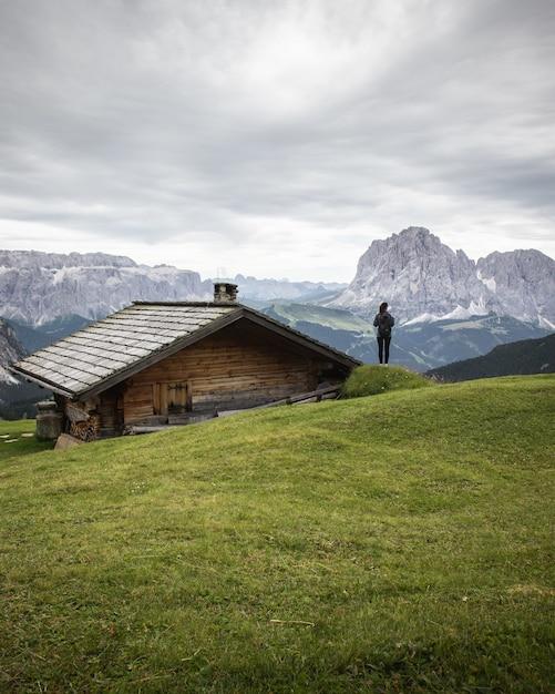 Prachtig shot van een houten huis en een persoon in het natuurpark puez-geisler in miscì, italië Gratis Foto
